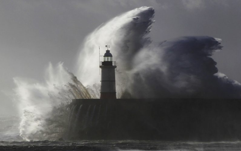 Waves crash against a lighthouse during storms that battered Britain and where a 14-year-old boy was swept away to sea at Newhaven in South East England October 28, 2013. Britain's strongest storm in a decade battered southern regions on Monday, forcing hundreds of flight cancellations, cutting power lines and disrupting the travel plans of millions of commuters. Police said rescuers were forced to call off a search for the boy late on Sunday due to the pounding waves, whipped up by the rising wind.