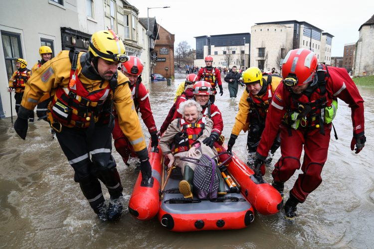 An elderly woman is rescued from her flooded home in York, North Yorkshire, after both the River Ouse and Foss burst their banks in dramatic fashion.